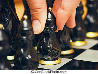 Person fingers with black pawn makes first move on chess board.