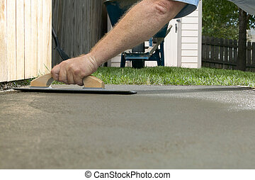Person finishing wet cement in a backyard project