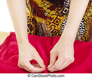 Person folding red blouse