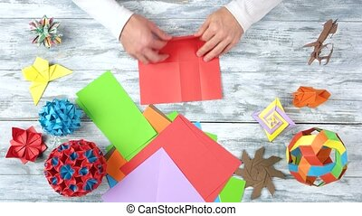 Person folding red paper sheet. Set of origami crafts made...