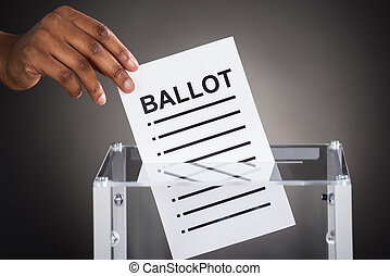 Person Hand Inserting Ballot In Box - Close-up Of A Person...