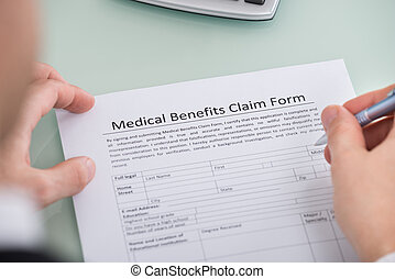 Person Hand Over Medical Benefits Claim Form