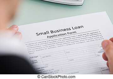 Person Hand Over Small Business Loan Application Form