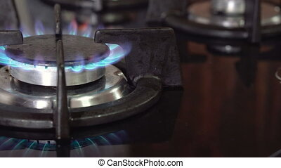 Person hand switching on kitchen stove burner. Blue gas...