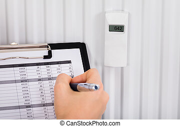 Person Hand With Clipboard Checking Digital Thermostat -...