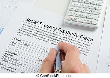 Person Hand With Pen Filling Social Security Disability Form...