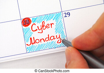 Person hand with pen writing Cyber Monday in calendar - ...