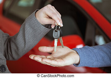 Person handing keys to someone else in a car shop