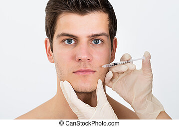 Person Hands Injecting Syringe On Man Face