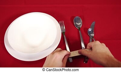 Person hands throw silver cutlery on red tablecloth closeup