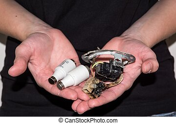 Person holding a damaged electric socket with a pair of...