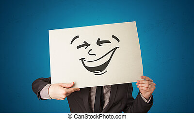 Casual person holding a paper with cool emoticon in front of his face