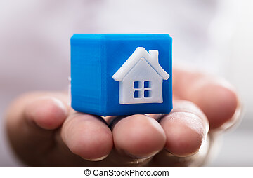 Person holding cubic block with house model