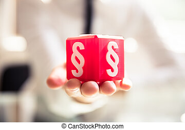 Person Holding Cubic Block With Paragraph Symbol