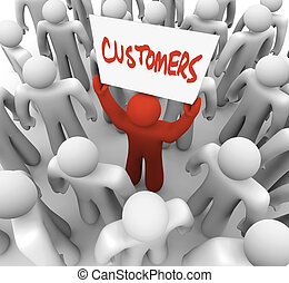 Person Holding Customers Sign in Crowd - A red person stands...