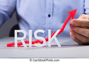 Person Holding Increasing Arrow Behind The Risk Text