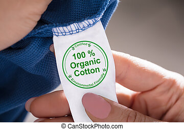 Person Holding Label Showing 100 Percent Organic Cotton
