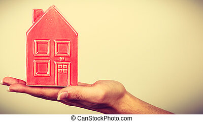 Person holding little red house, household concept