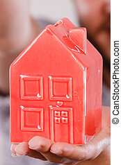 Person holding little red plastic house