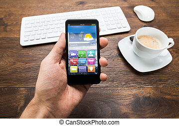 Person Holding Mobile Phone With Tea Cup On Desk