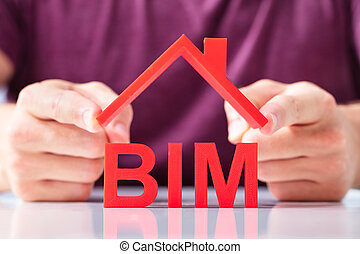 Person Holding Roof Over BIM Text