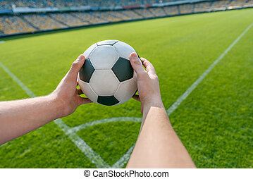 person holding soccer ball on soccer field stadium