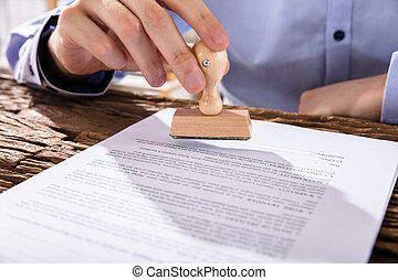 Person Holding Stamp On Document