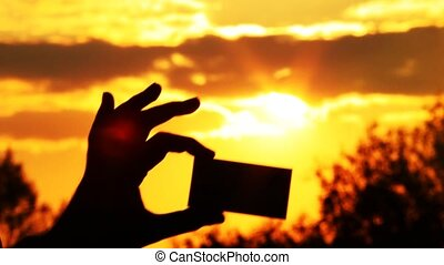 person holds a card in a hand opposite to the sun