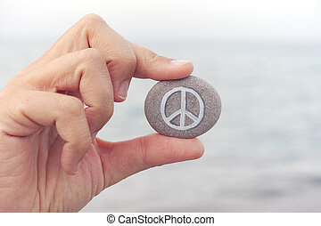 Person holds stone with peace symbol against sea in background