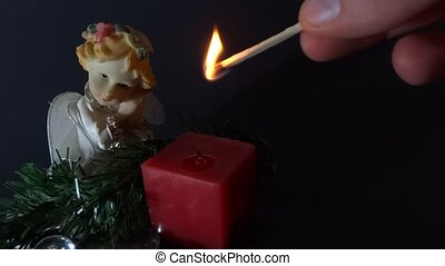 person igniting a candle with angel figurine