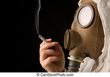 Person in gas mask smoking cigarette on dark background