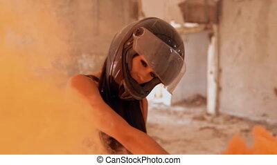 close up face woman biker posing looking camera waving orange smoke grenade slow motion