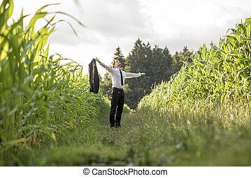 Person in necktie standing in between rows of corn