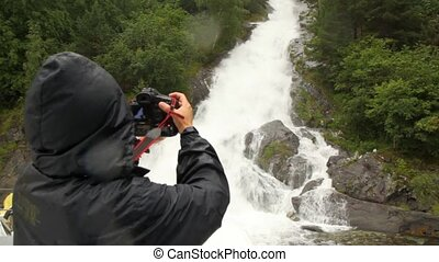 person in raincoat photographs falls on wood rocks