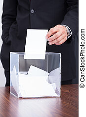 Person Inserting Ballot In Box