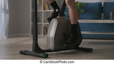 person is training alone in home, using stationary bike for keeping fit, closeup of legs on pedals, fitness and wellness concept