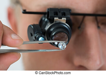 Person Looking At Diamond With Magnifying Loupe - Close-up...