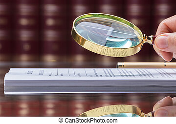 Person Looking At Document With Magnifying Glass