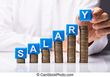 Person Making Salary Word On Stacked Coins