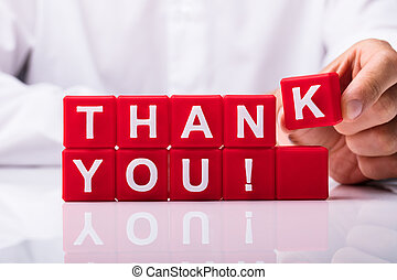 Person Making Thank You Text With Red Cubic Blocks