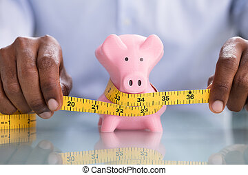 Person Measuring Pink Piggybank With Measure Tape