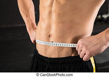 Person Measuring Waist Using Measuring Tape