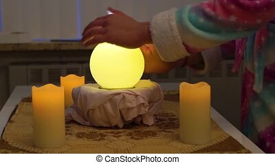 person moving hands around a lighted fortune teller sphere, traditional spirituality and witchcraft
