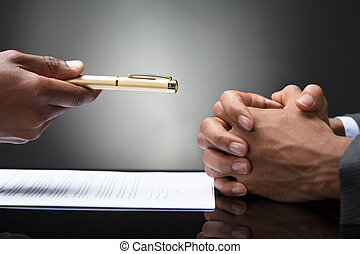 Person Offering Pen To The Other Person With Clasped Hand