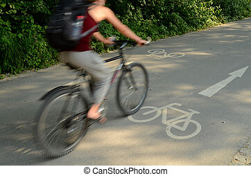 Motion Blur Of A Cyclist On A Cycle Lane On A Sunny Day