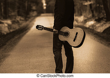 Person on the path with guitar. Free travel with country instrument in forest.