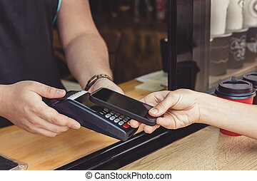 Person paying pay through smartphone using NFC technology in...
