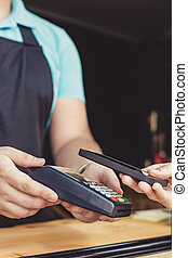 Person paying pay through smartphone using NFC