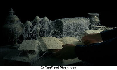 Person Picks Up Book From Under Cobwebs