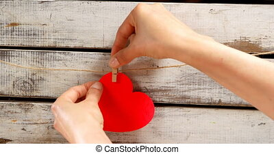 Person pinned a red colour paper heart against wooden surface 4k